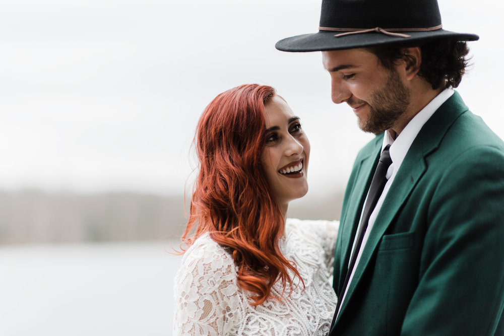Bride in lace and beaded crop top and groom in green jacket and black fedora smiling at each other.
