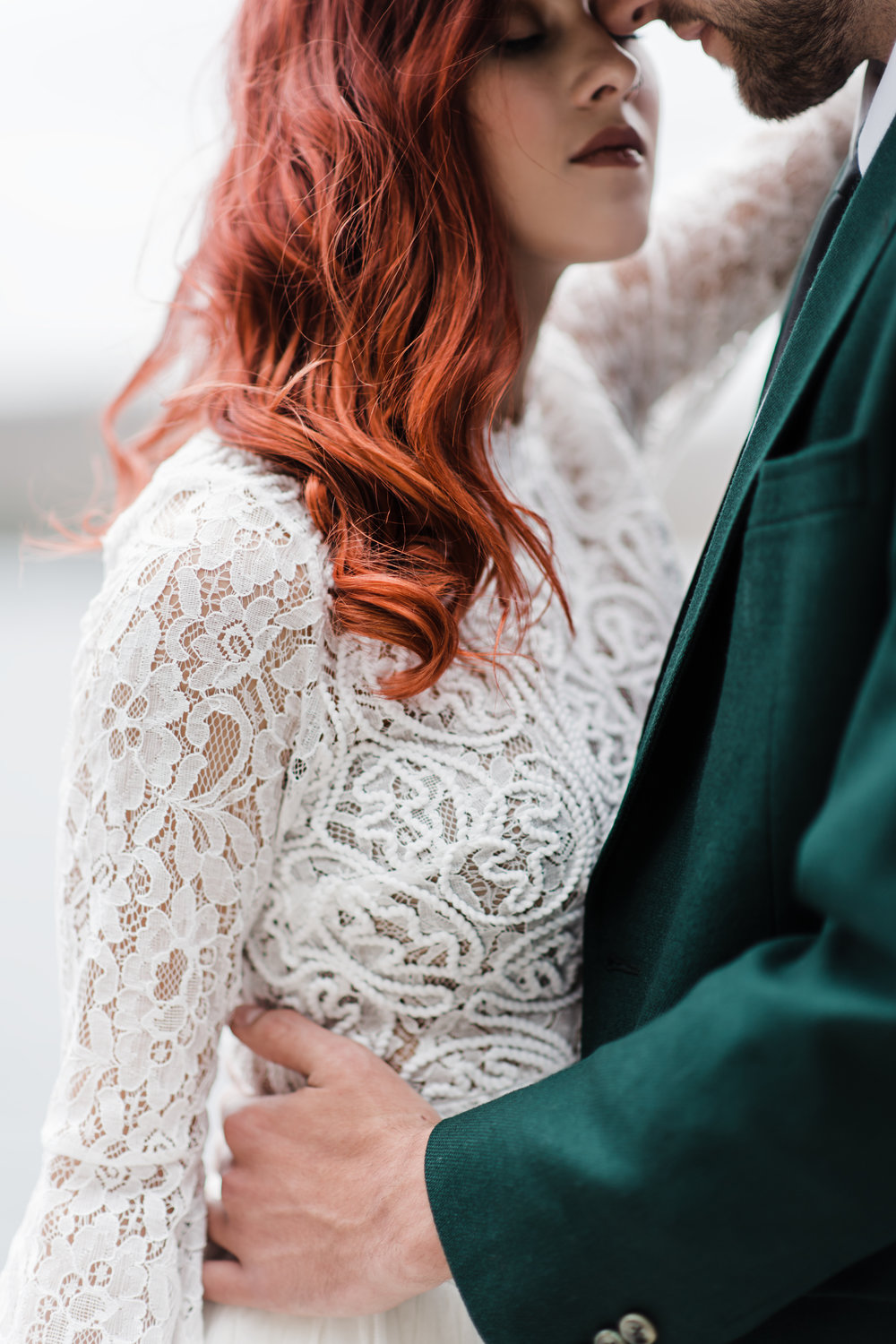 Groom in green jacket with hands around the waist of bride with curly red hair in lace and beaded crop top.