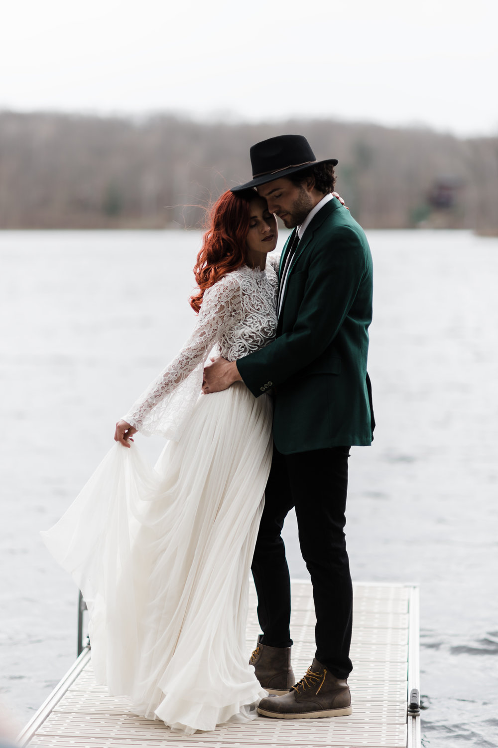 Groom in green jacket and black fedora and bride in lace and beaded crop top and flowing skirt standing on a dock.
