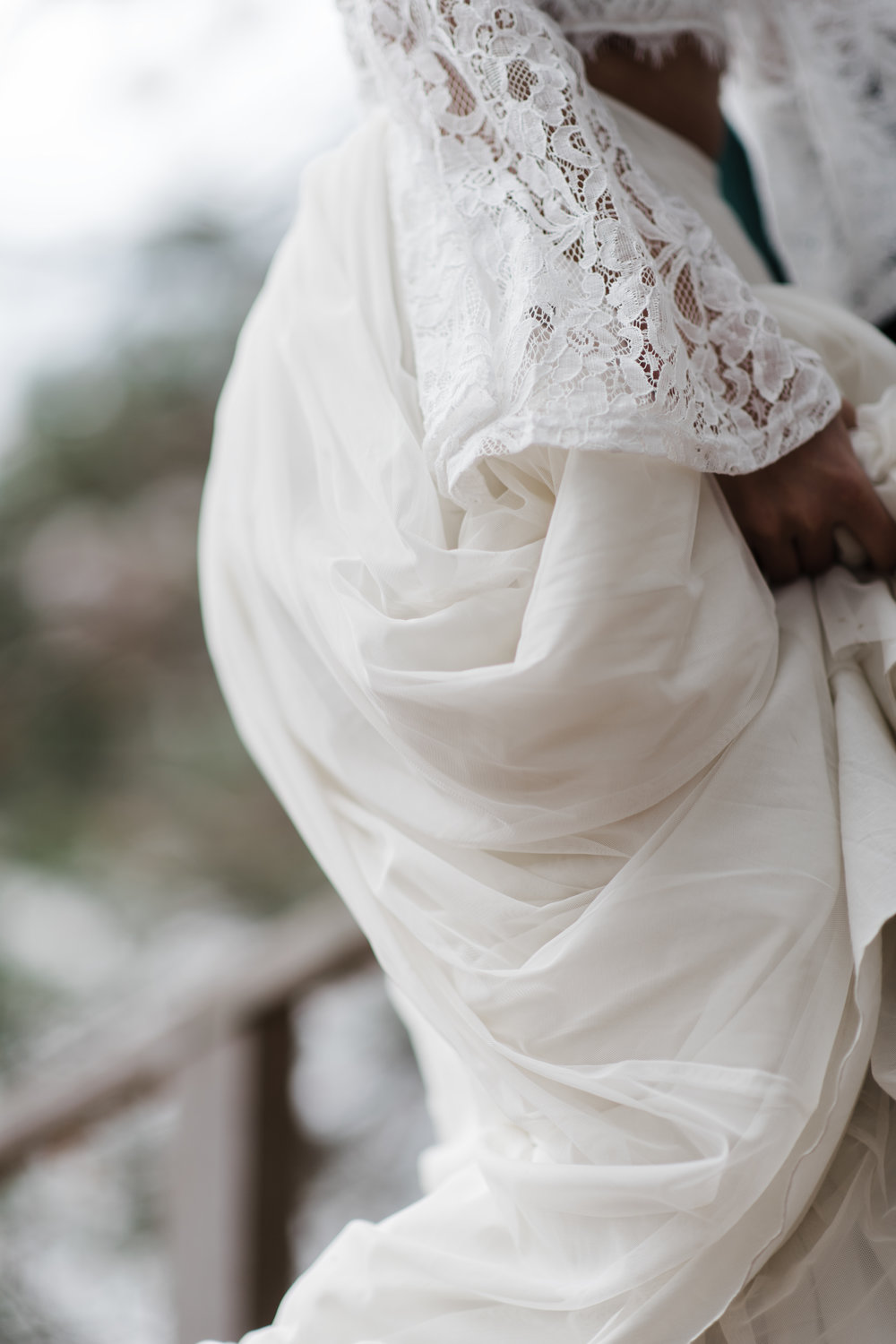 Bride holding on to her long flowing skirt.