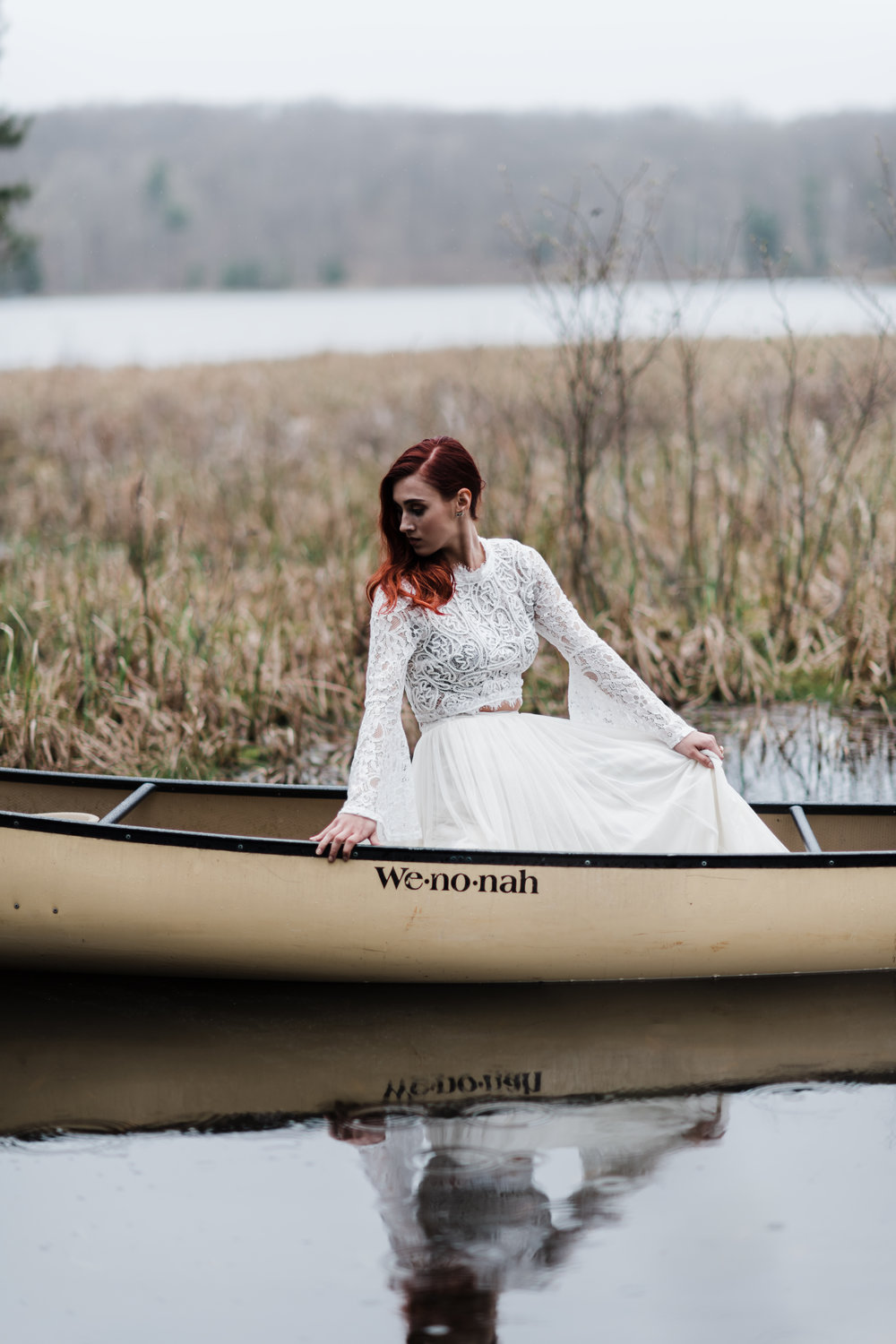 Bride in lace and beaded crop top and flowing skirt sitting in a canoe with reflection in the water.