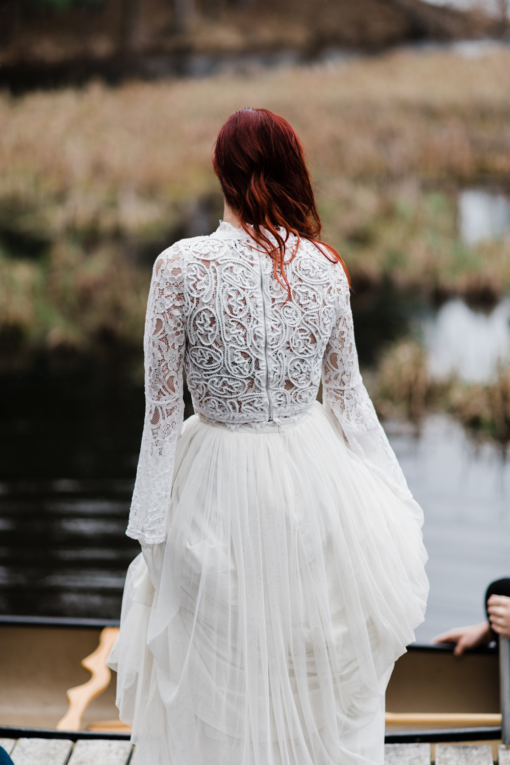 Bride in lace and beaded crop top and flowing skirt standing on a dock and looking at groom in a canoe.