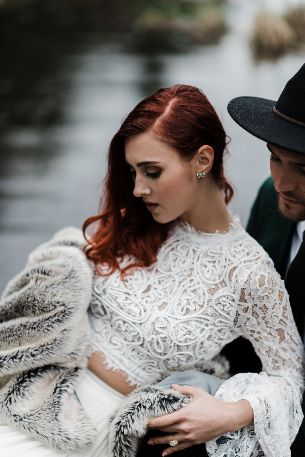 Bride in lace and beaded crop top and fuzzy blanket and soft pink ring leaning back against groom in green jacket and black fedora.