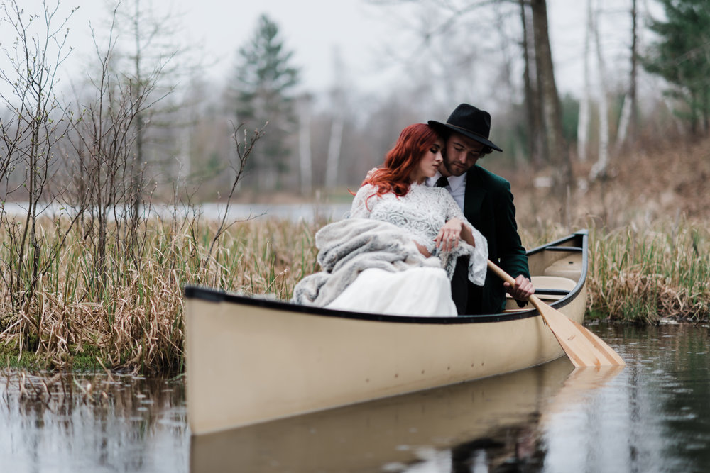 Bride in lace and beaded crop top and fuzzy blanket and soft pink ring leaning back against groom in green jacket and black fedora rowing a canoe.