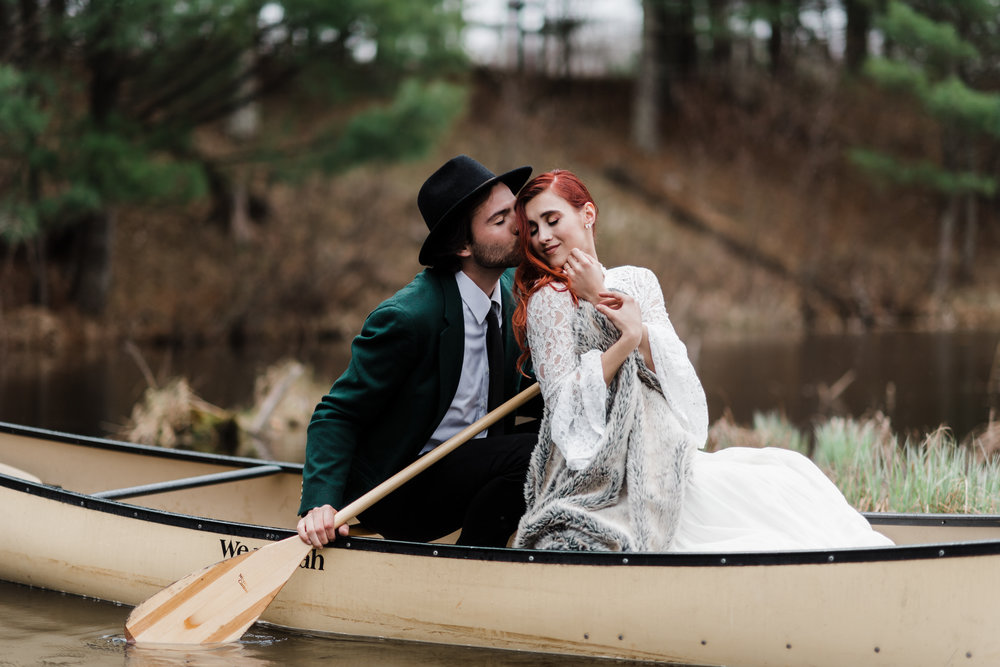 Groom in green jacket and black fedora kissing bride in lace and beaded crop top sitting in a canoe.