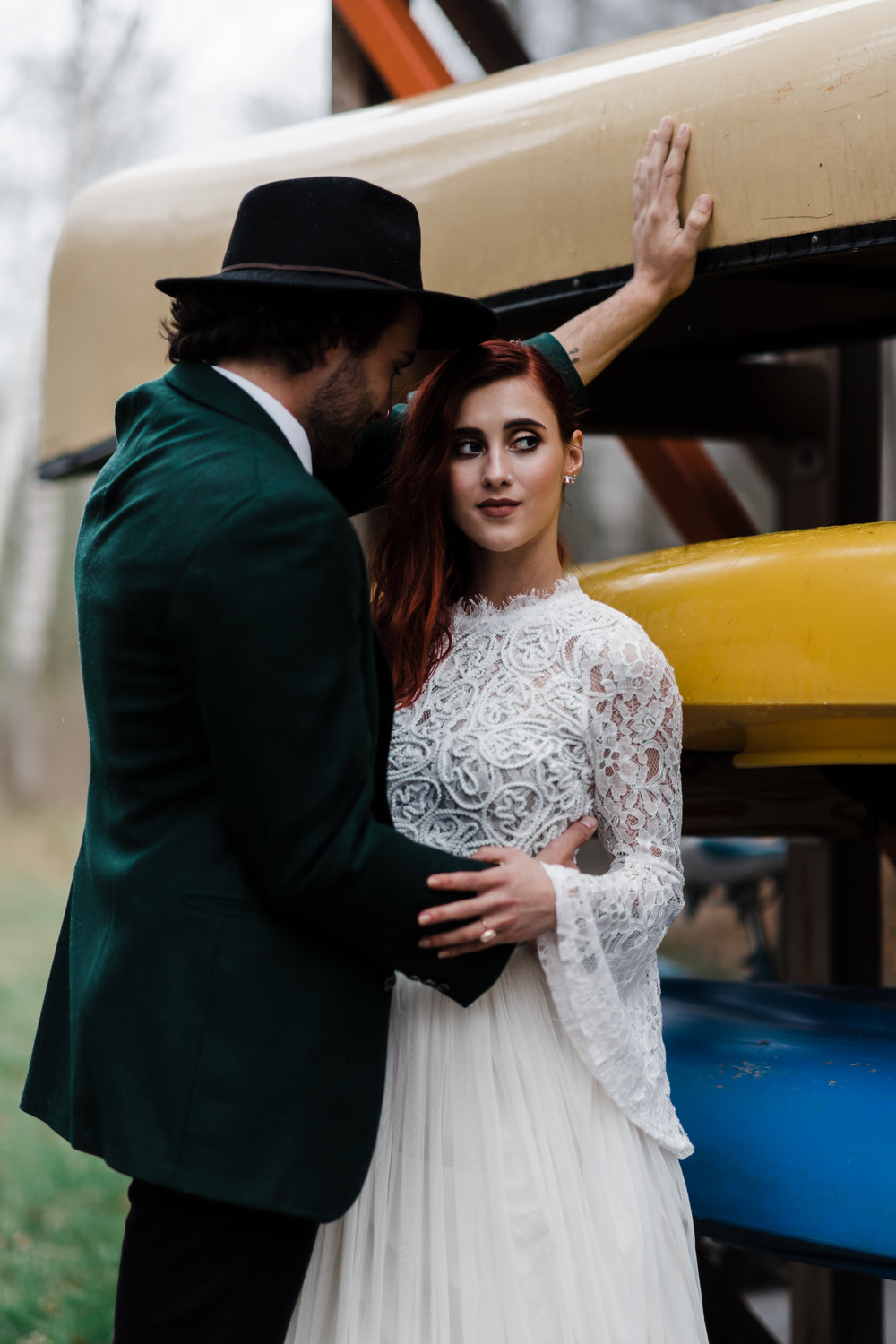 Groom in green jacket and black fedora leaning into bride in lace and beaded crop top and flowing skirt in front of colorful canoes.