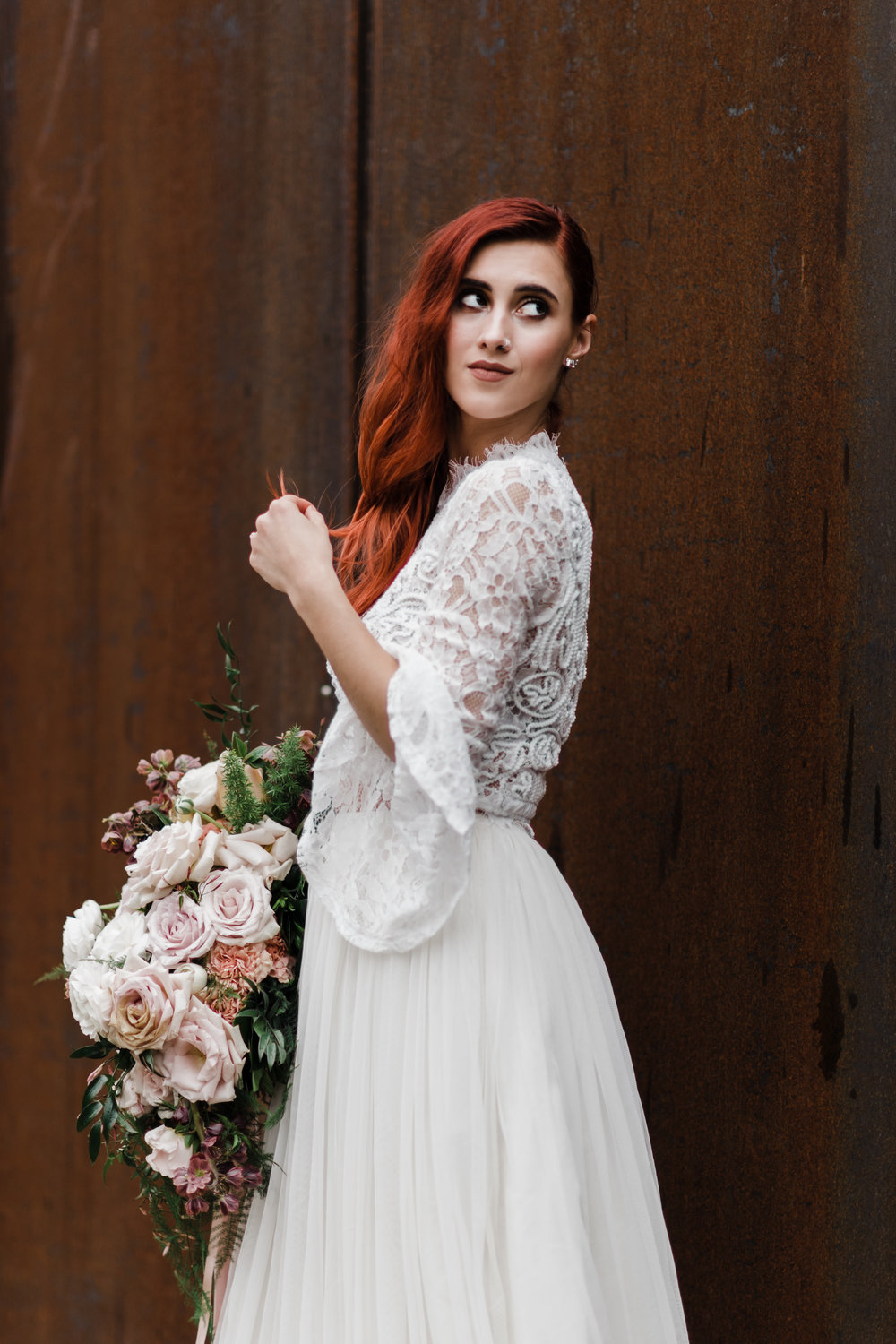 Bride in lace and beaded crop top and flowing skirt holding bouquet and standing in front of a rusty metal wall.