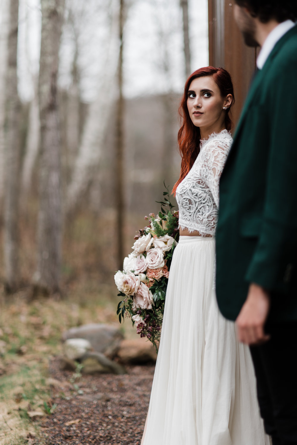 Bride in lace and beaded crop top and flowing skirt holding bouquet in one hand and groom's hand in the other.
