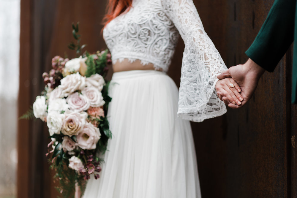 Bride in lace and beaded crop top and flowing skirt holding bouquet in one hand and groom's hand in the other with focus on her soft pink ring.
