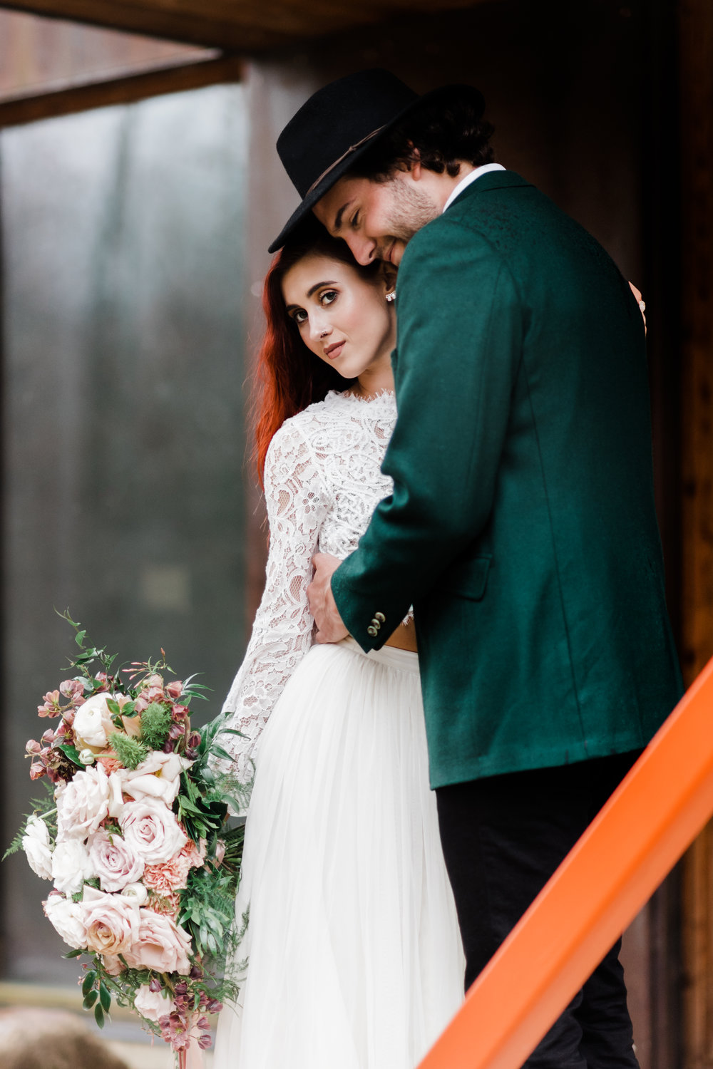 Groom in green jacket and black fedora smiling while holding onto bride in lace and beaded crop top and flowing skirt.