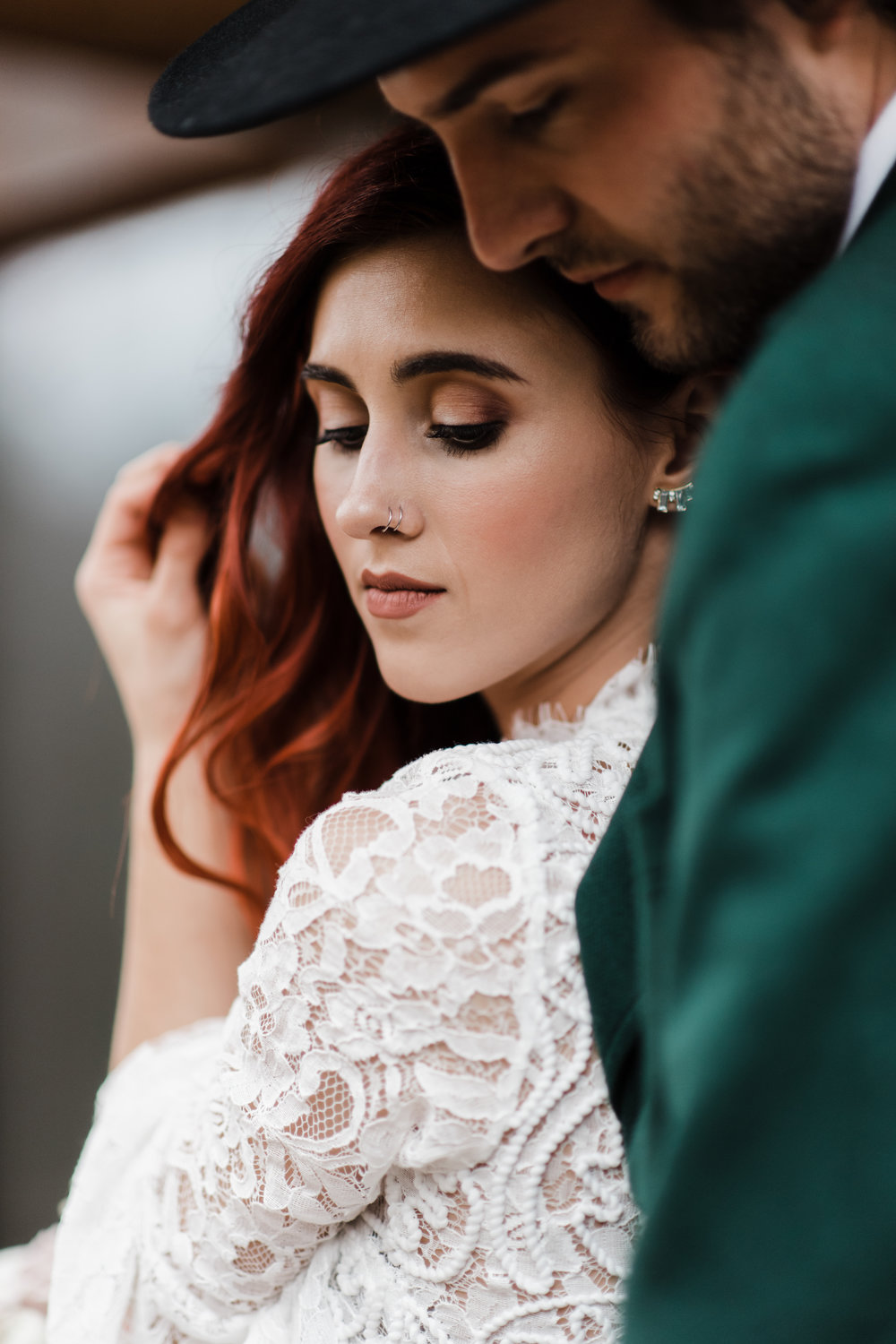 Bride with soft brown eyeshadow and nose rings wearing lace and beaded crop top and running hand through her read curly hair.