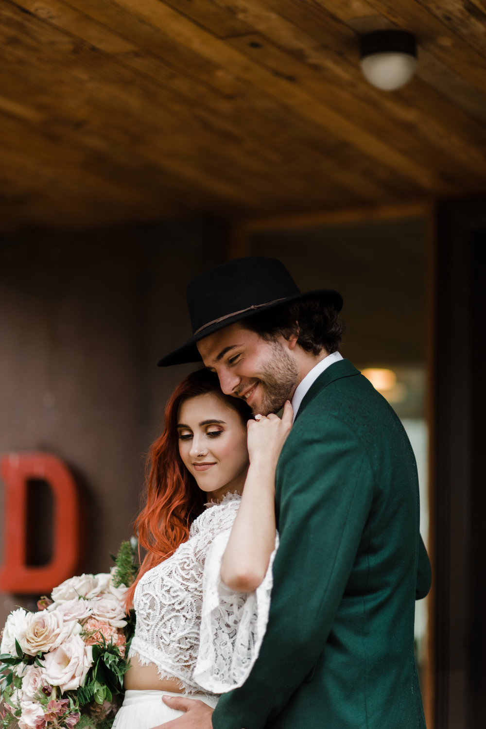 Groom in green jacket and black fedora smiles as bride in lace and beaded crop top run her hand across his face.