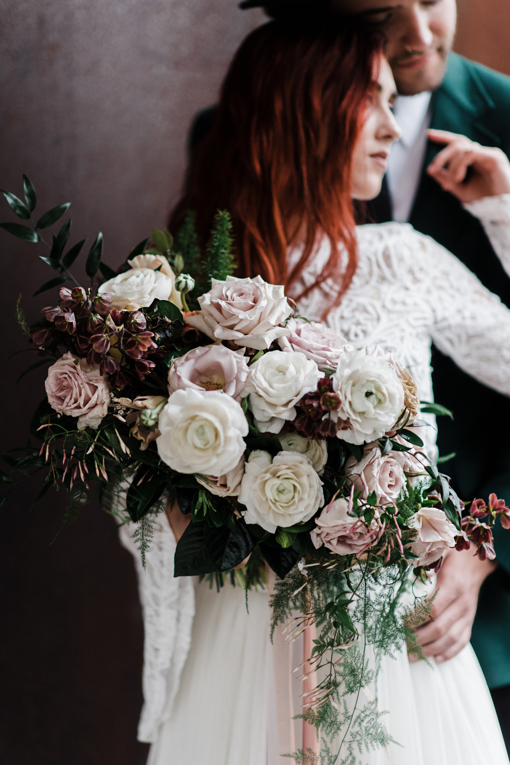 Bridal bouquet with soft pink roses and cream peonies and lush greens held by bride leaning back into groom.