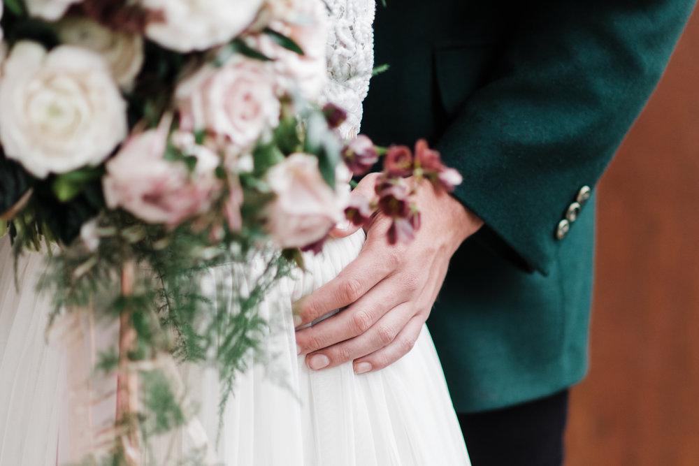 Groom in green jacket rests hand on bride's waist.