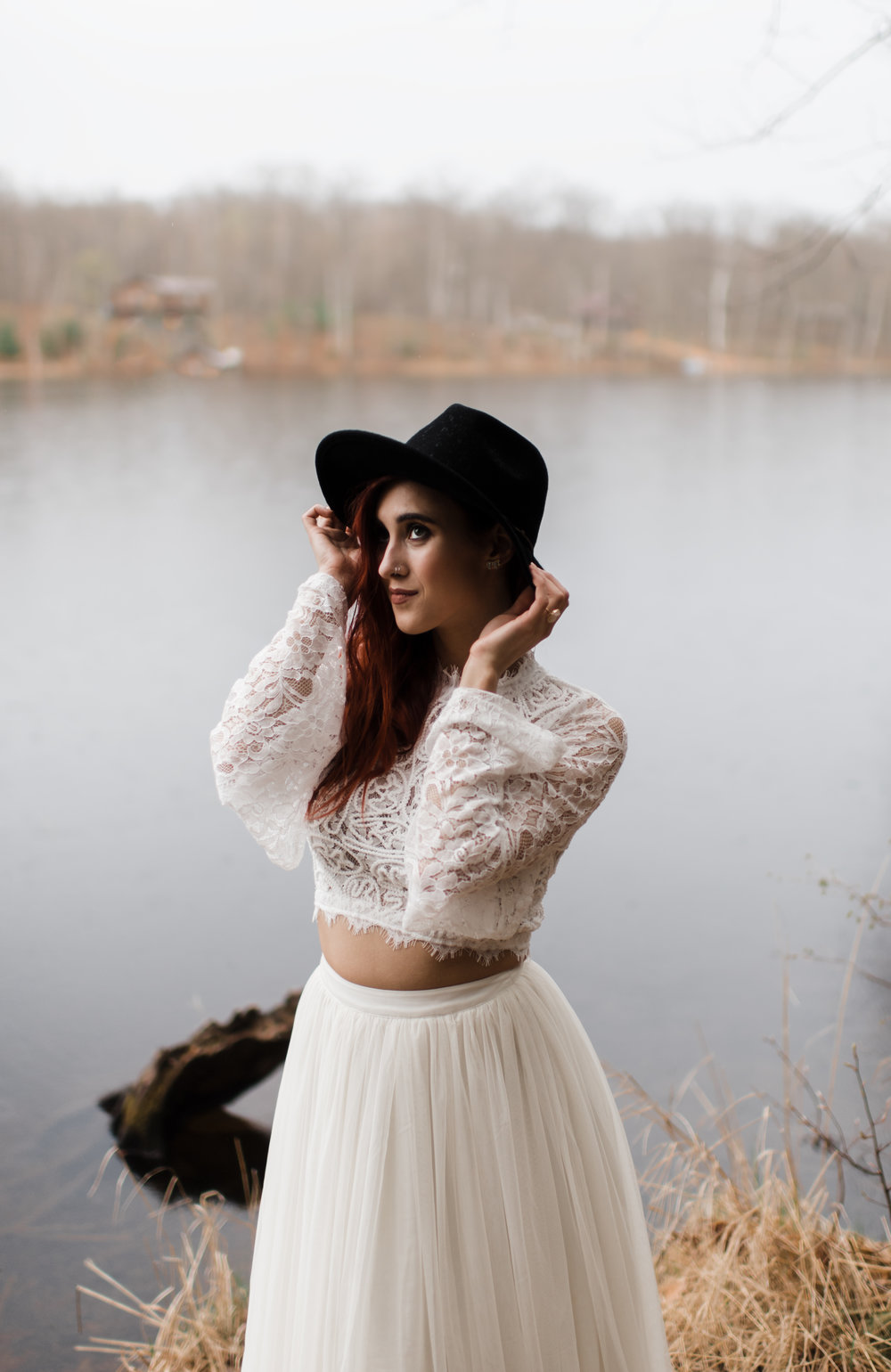 Bride in lace and beaded crop top and flowing skirt wears black fedora playfully.