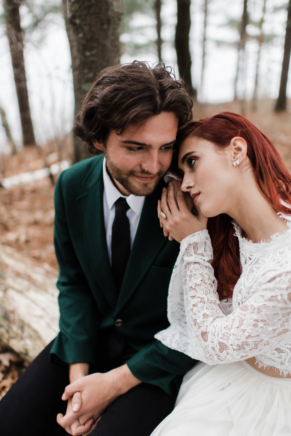 Bride in lace and beaded crop top rests hands on groom's shoulder and stares into his eyes.