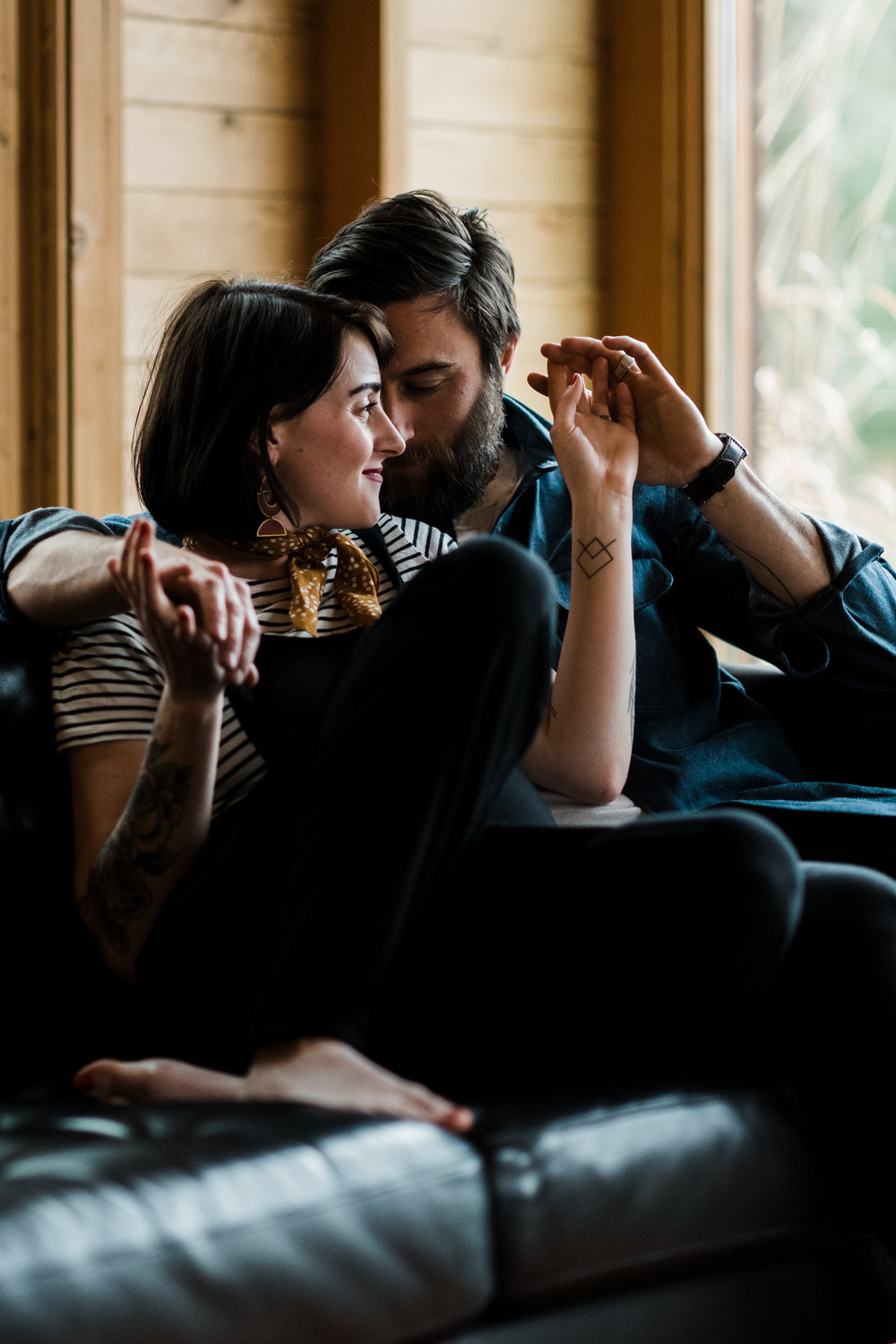 Photo of a couple sitting on a leather couch and holding hands at a cabin on Two Bear Lake in Weyerhauser, WI.