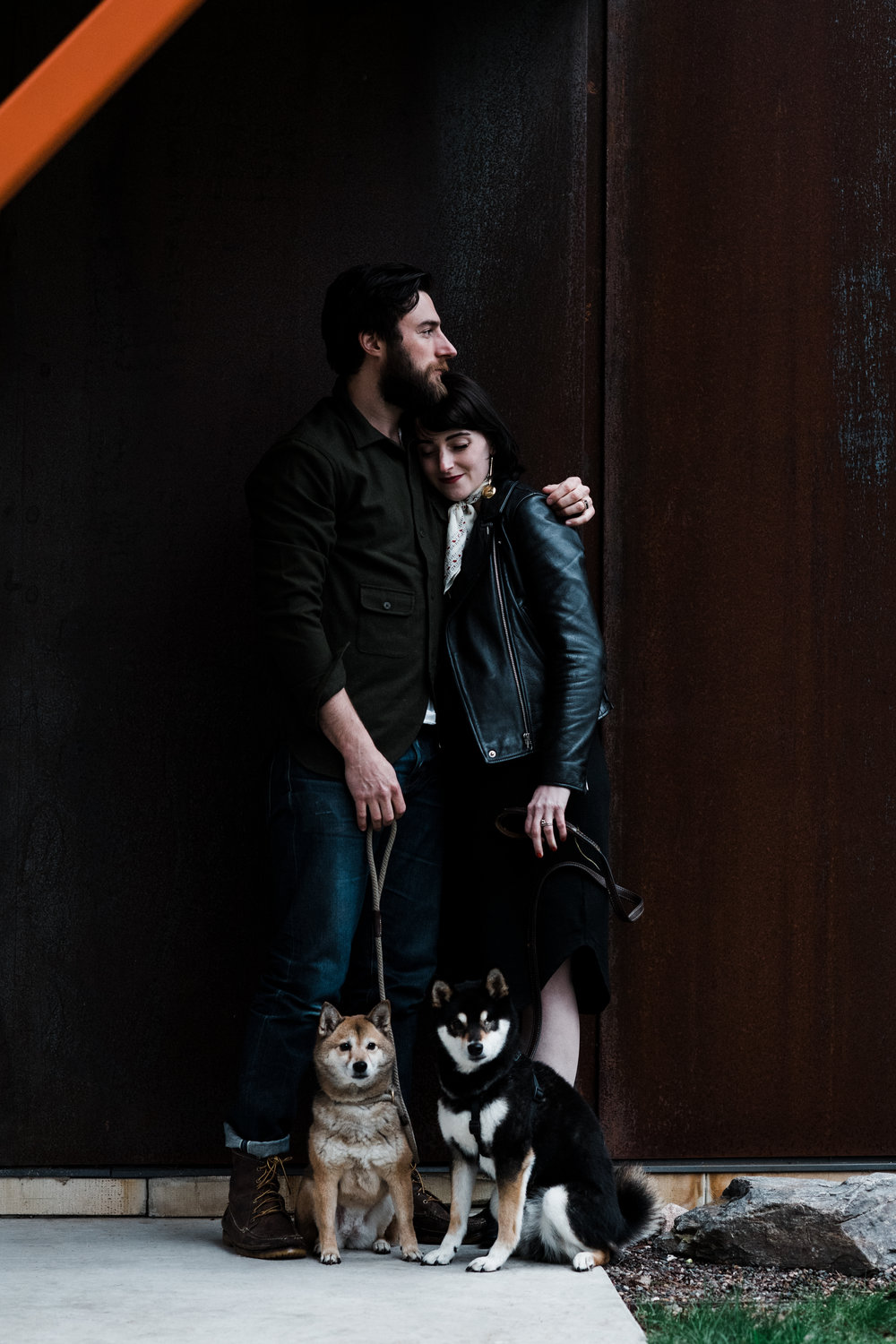 Photo of a couple standing by a brown wall with their dogs at a cabin on Two Bear Lake in Weyerhauser, WI.