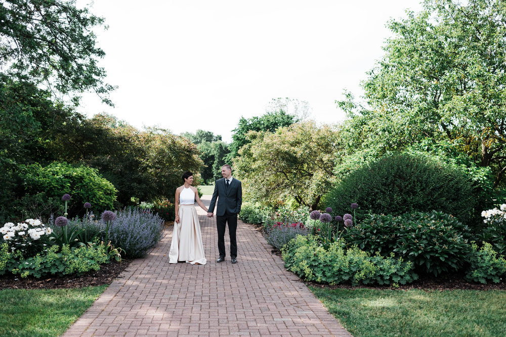 Bride and groom on a garden path holding hands and smiling at each other.