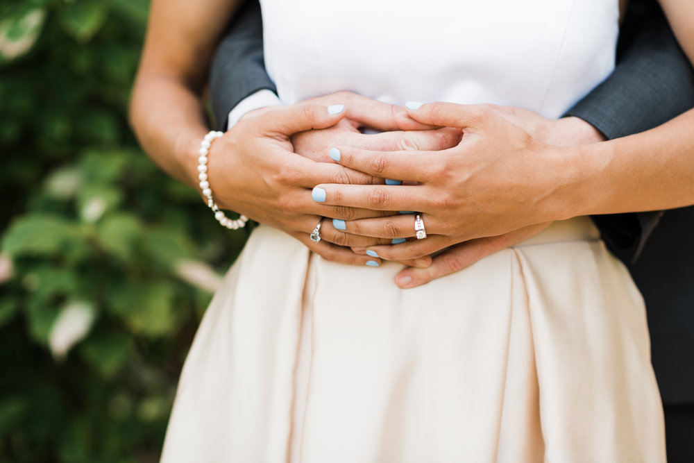 Groom wraps his hands around bride's waist as she holds his hands.