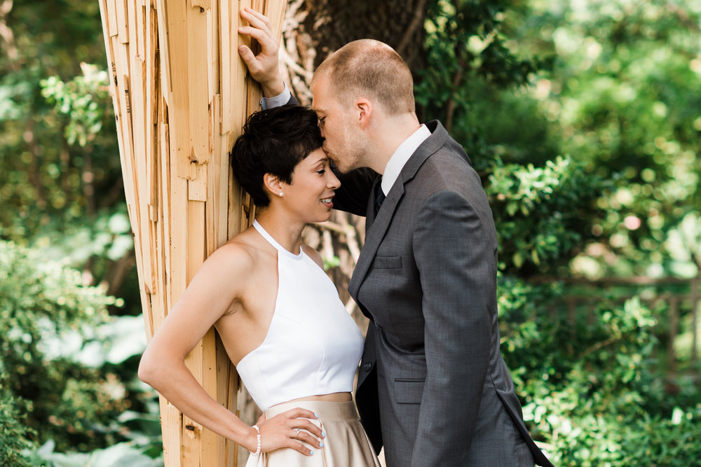 Groom leans into bride and kisses her forehead.