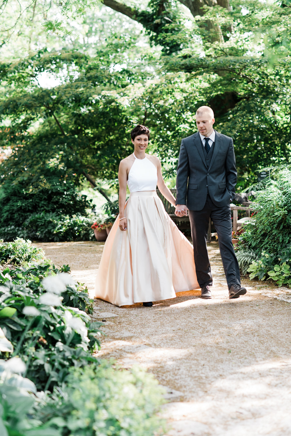 Bride and groom hold hands while walking down a garden path.