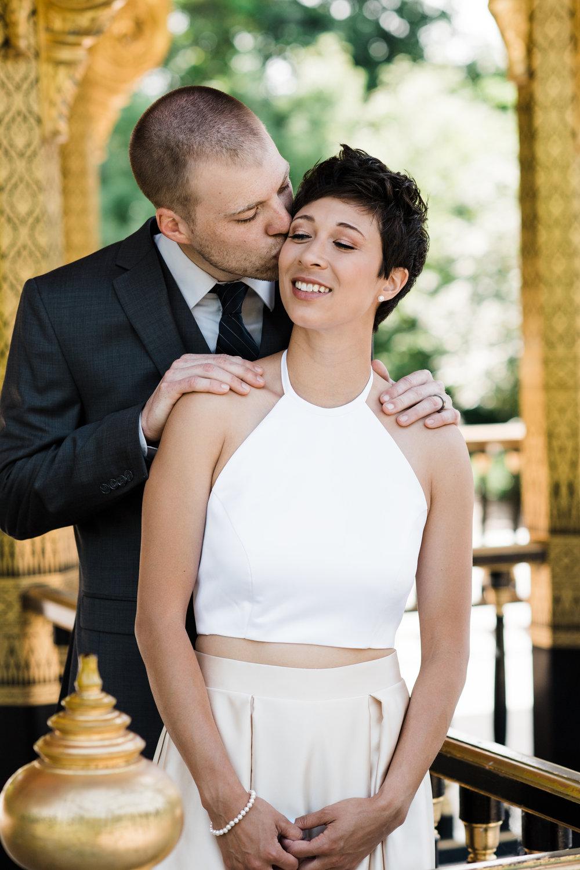 Groom kisses bride's temple.