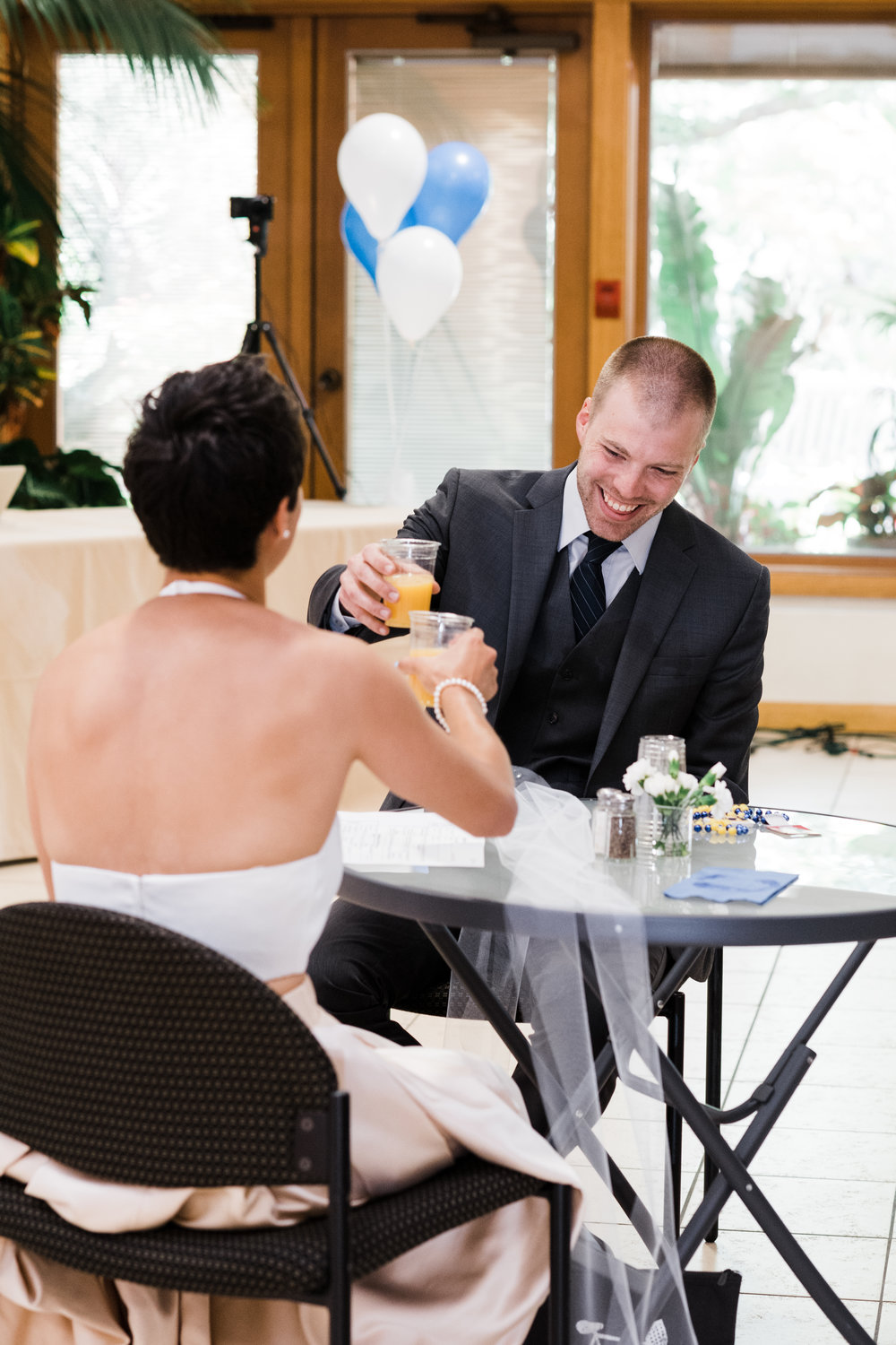 Bride and groom raise their cups to toast each other.