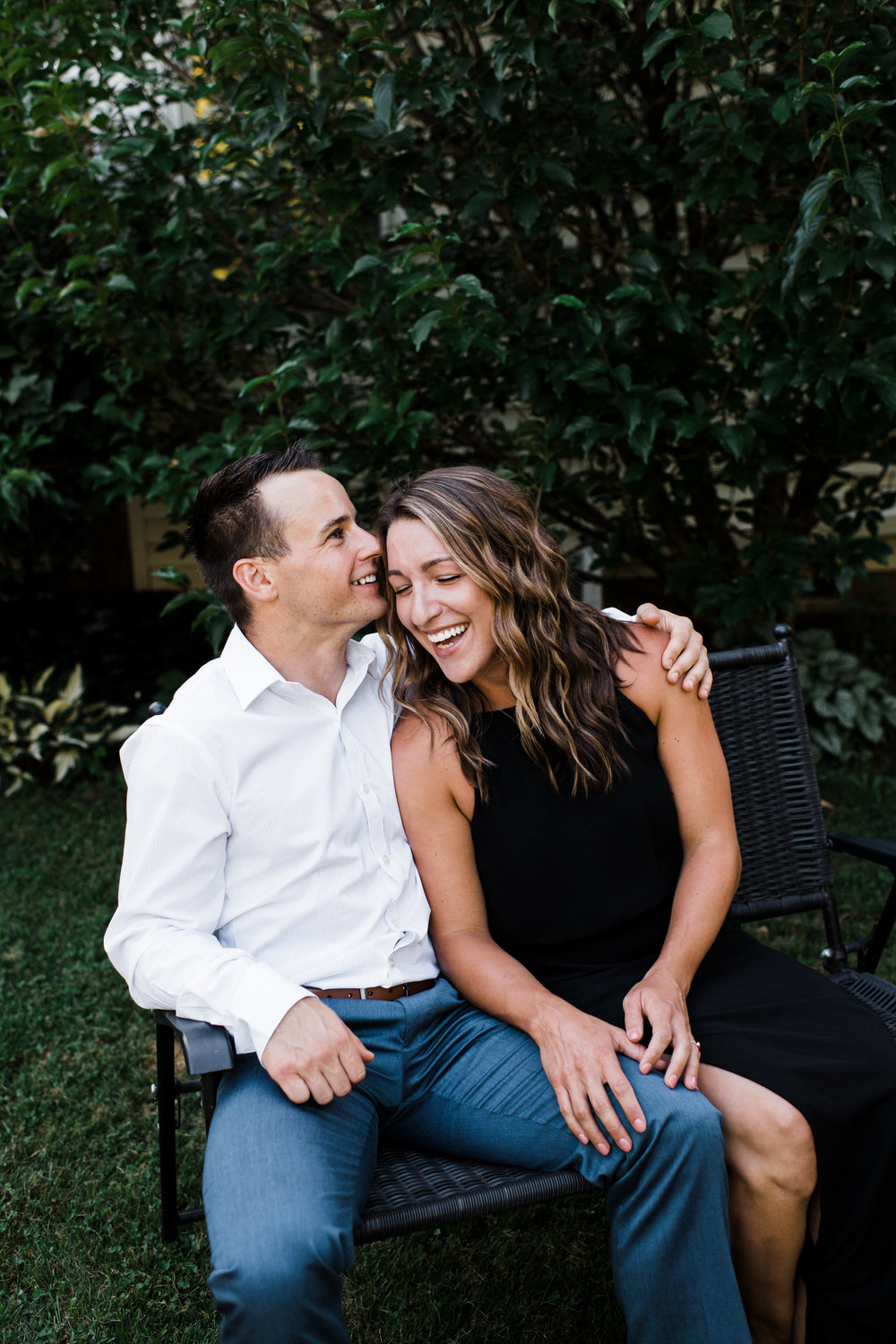 Engaged couple sitting on a bench in their backyard laughing.