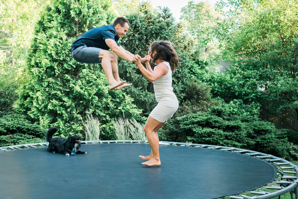 Engaged couple jumps high on a trampoline while their dog watches in amazement.