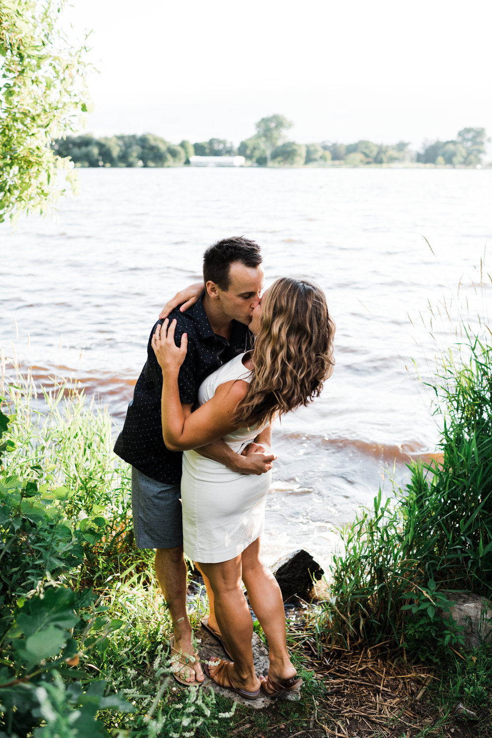 Man dips his fiancé back as he kisses her in front of the Fox River in Wisconsin.