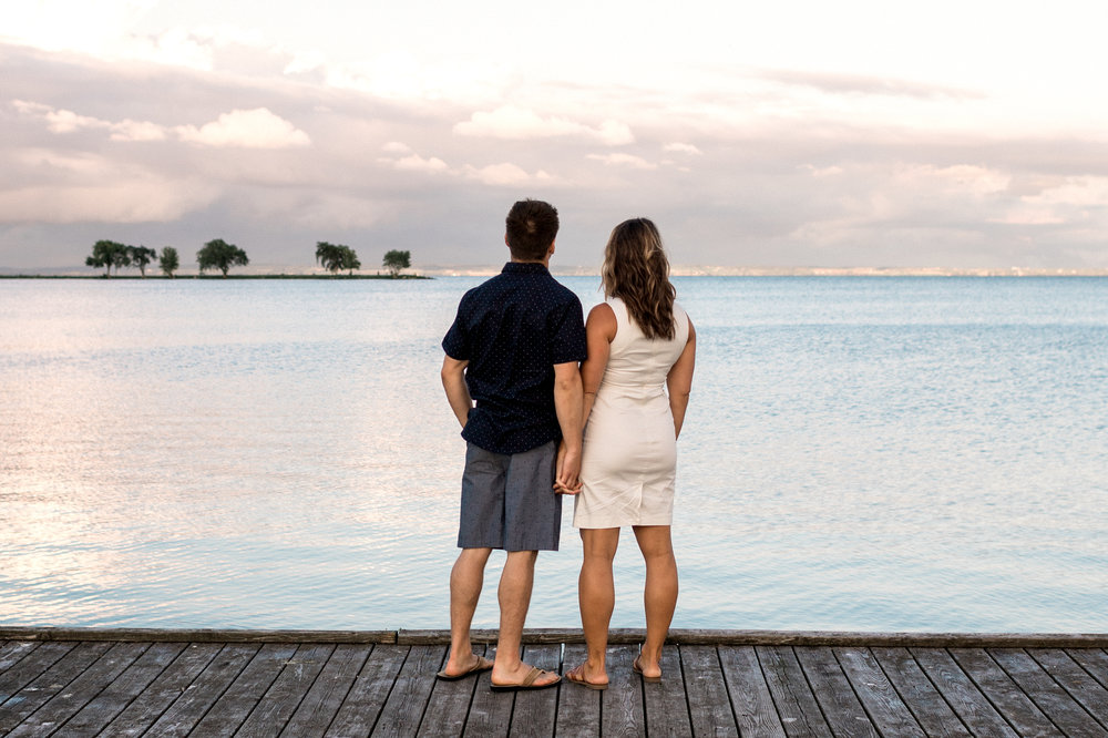 Engaged couple holds hands standing on a dock overlooking Lake Winnebago in Wisconsin.
