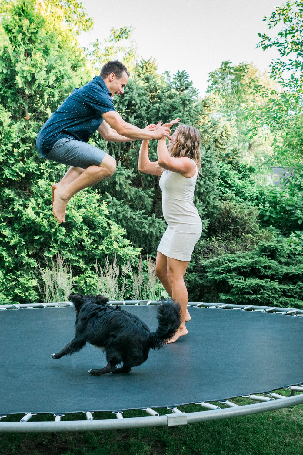 Engaged couple jumps on a trampoline with their black dog.