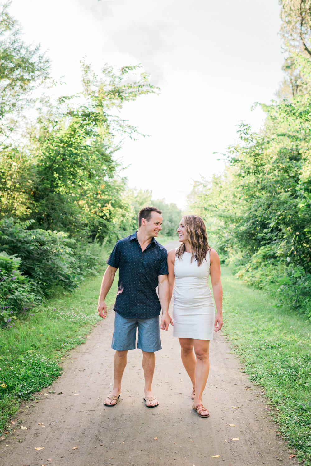 Engaged couple holds hands and looks into each other's eyes as they walk down a gravel road.