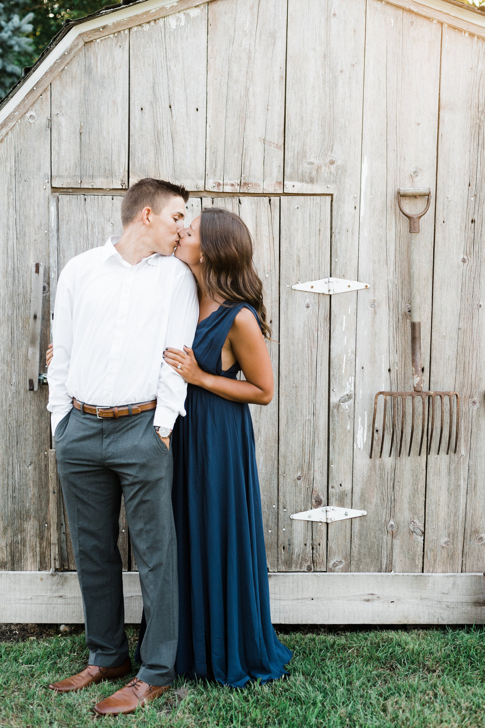 Engaged couple kisses in front of a shed with a pitchfork hanging on it.