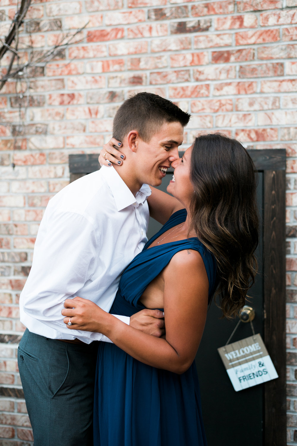 Engaged couple faces each other and laughs while rubbing noses in front of a brick wall.