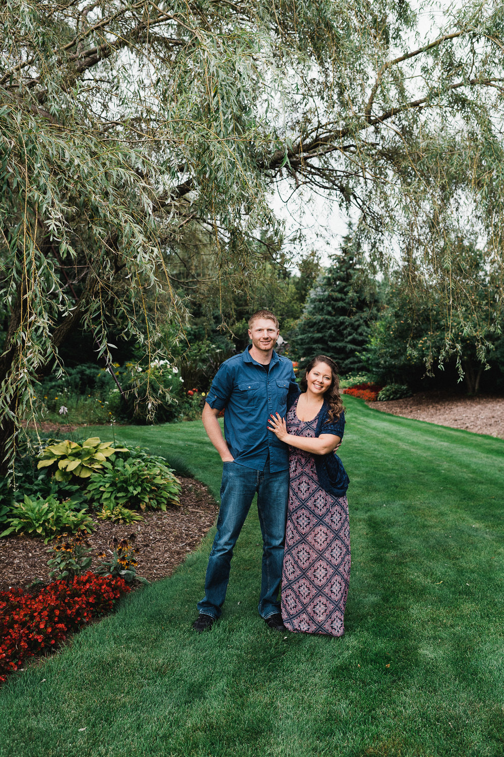 Engaged couple with arms around each other smiles while standing in a garden.