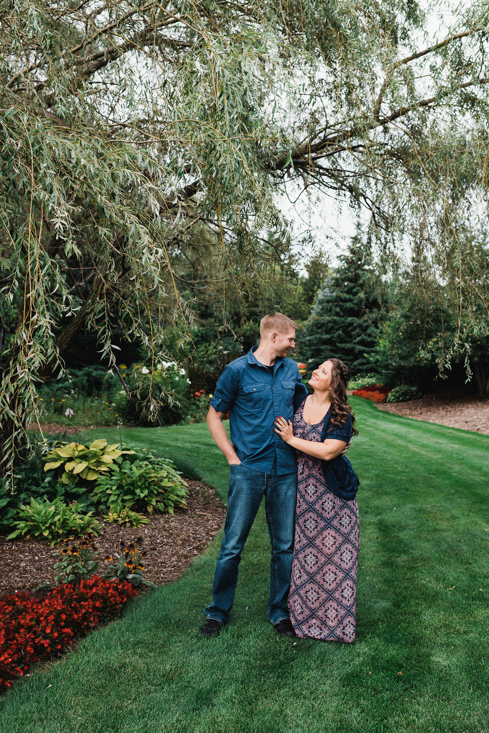 Engaged couple with arms around each other smiles at each other while standing in a garden.