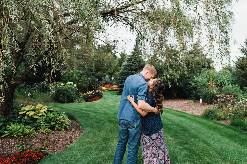 Engaged couple embraces each other and smiles as they lean in to kiss in a garden.