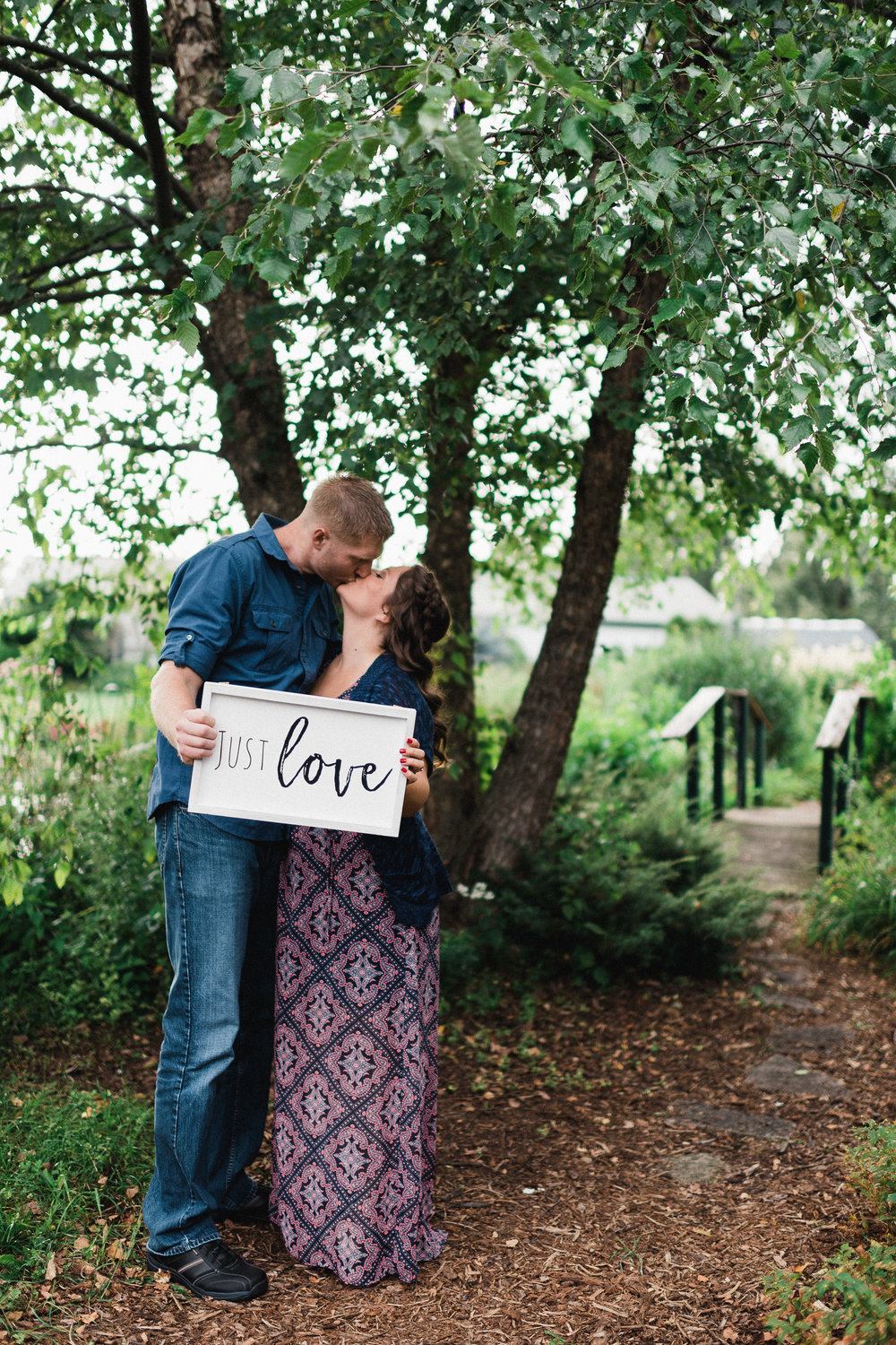 Engaged couple kisses while holding a sign that says Just Love.