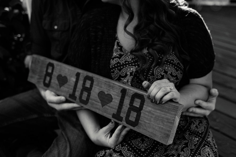 Engaged couple holds a homemade wooden sign with their wedding date painted on it.
