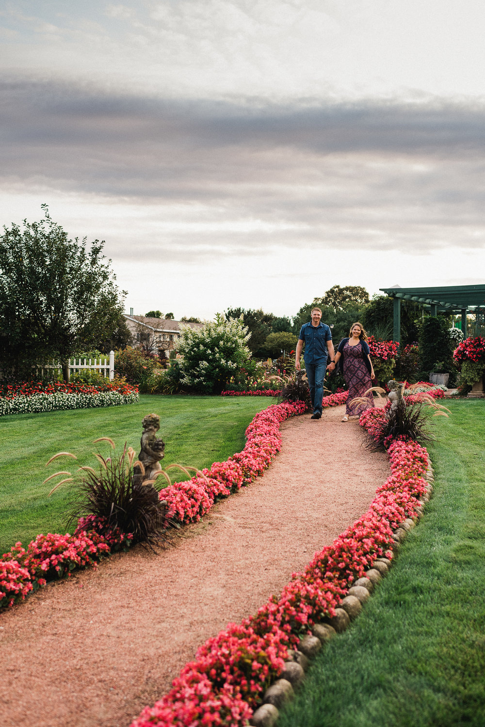 Engaged couple walks holding hands along a garden path lined with pink flowers.
