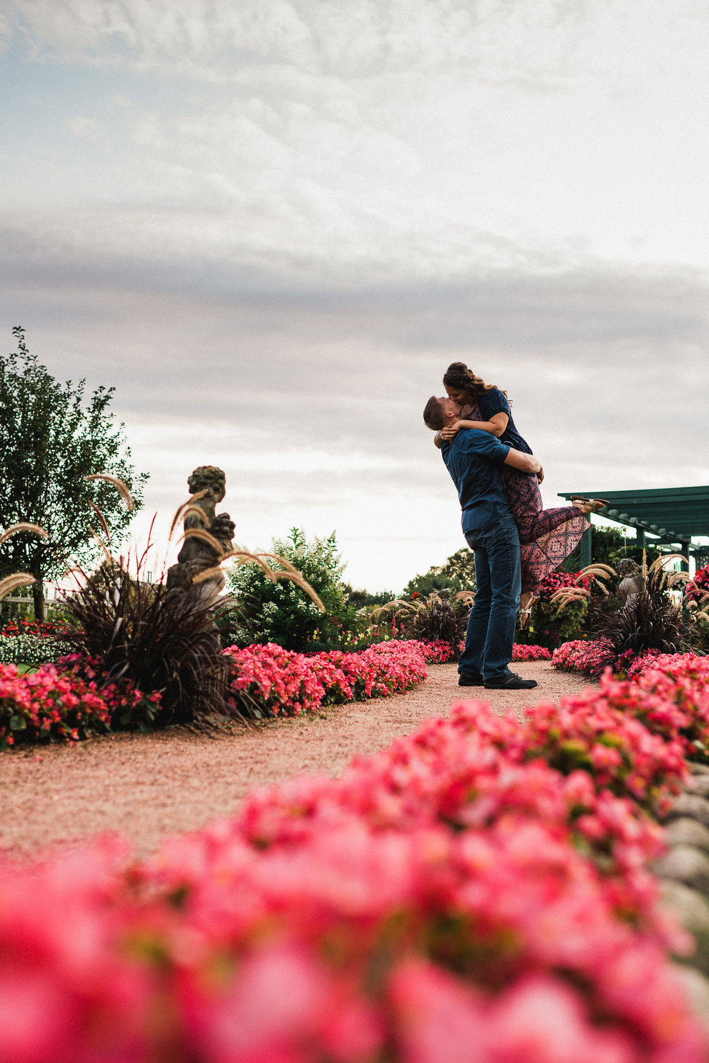 Man lifts his fiance up and kisses her on a garden path lined in pink flowers.