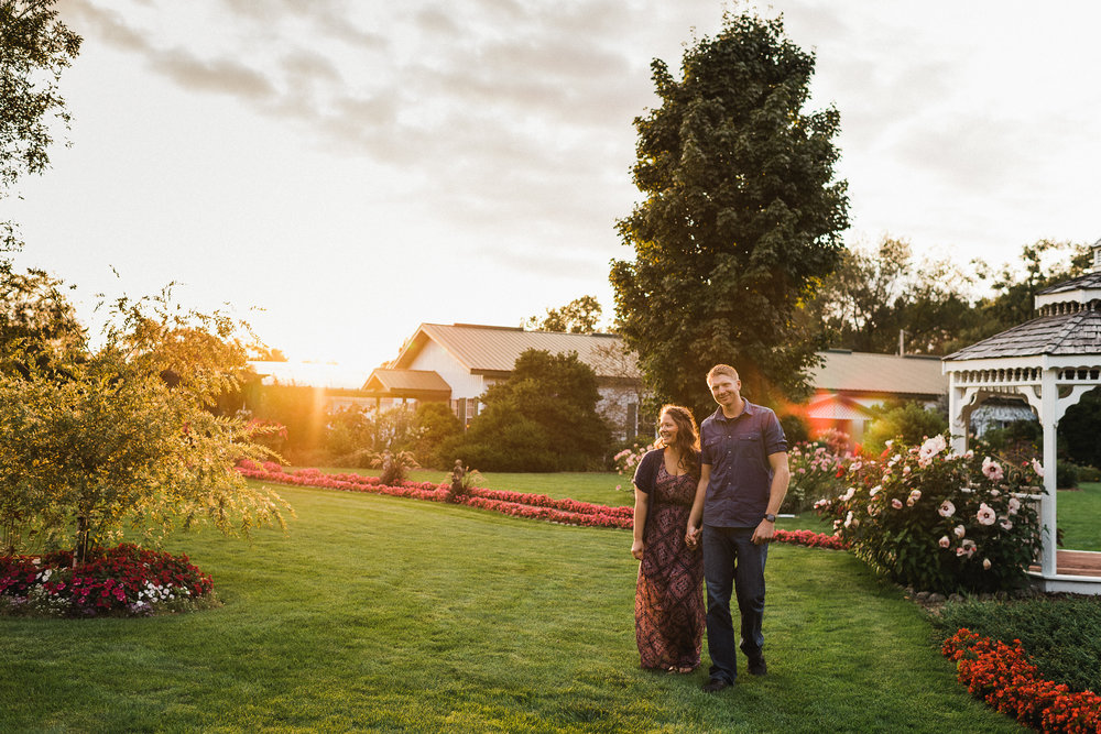 Woman holds her long dress and her fiance's hand as they walk through a garden.