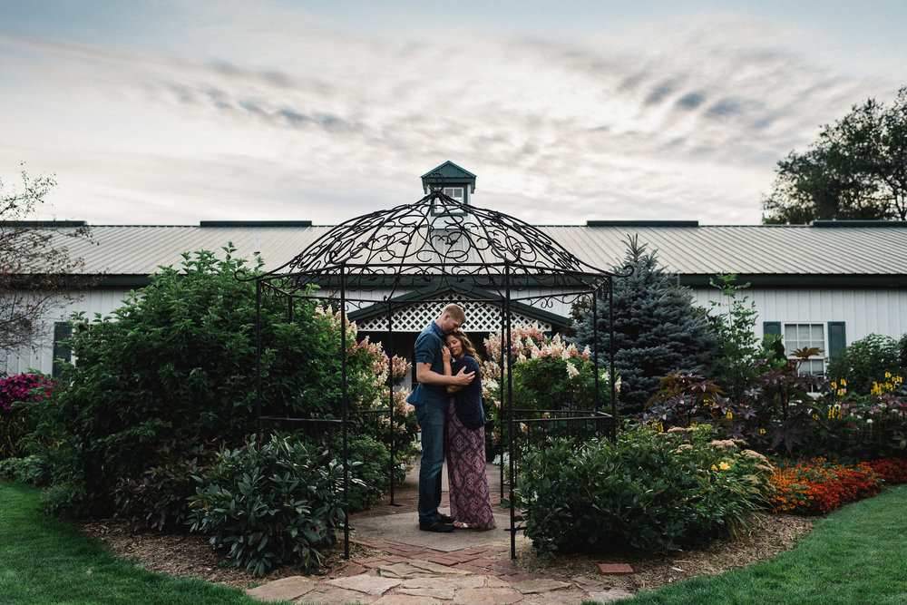 Engaged couple embrace each other with eyes closed inside a metal gazebo surrounded by plants and bushes.