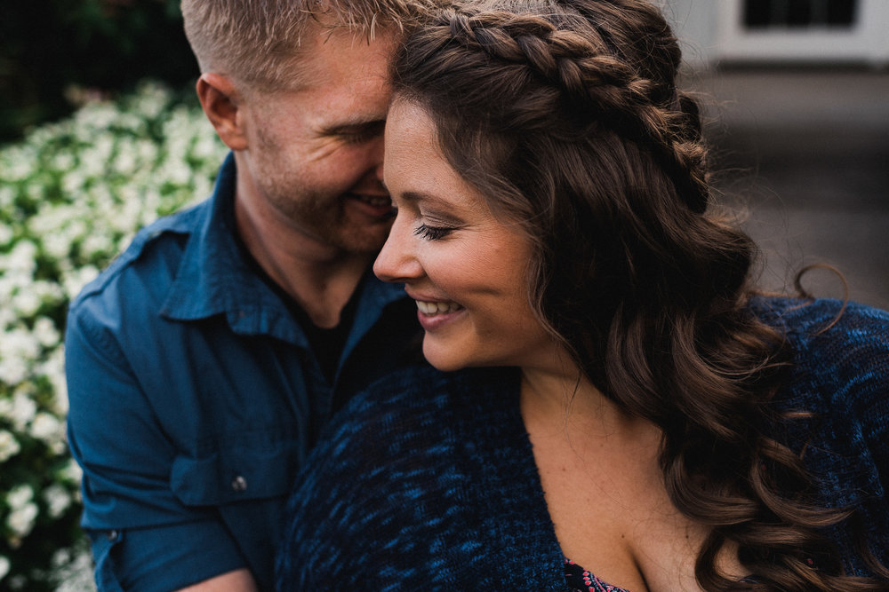 Woman with braid in her hair smiles as her fiance whispers in her ear.