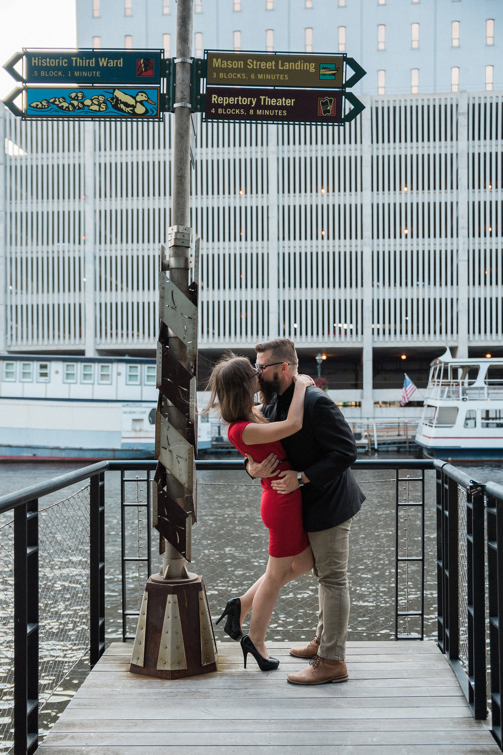 Man dips his fiance back as he kisses her on a dock under a sign to Historic Third Ward, Mason Street Landing, and Repertory Theater.
