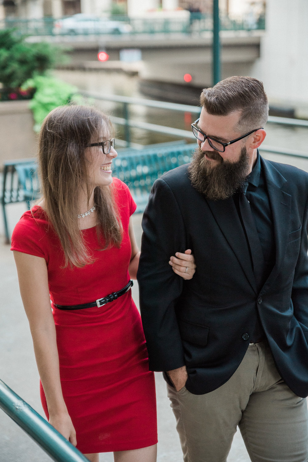 Woman in fitted red mini dress holds on to her fiance's arm and laughs while they look at each other.