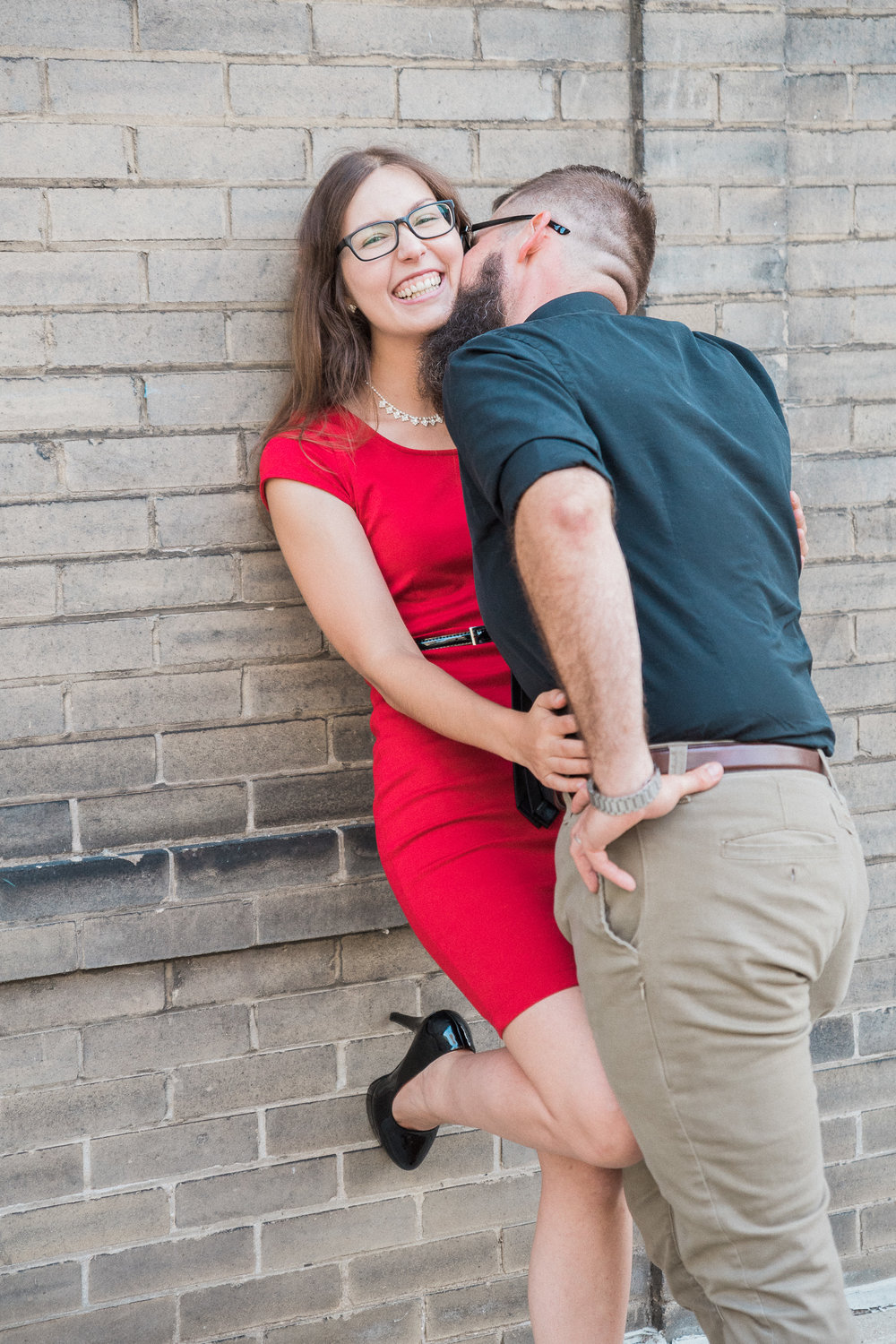 Woman smiles and leans back into a brick wall as her fiance kisses her neck.