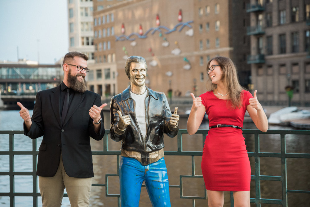 Engaged couple mimic The Bronze Fonz on the Milwaukee Riverwalk.